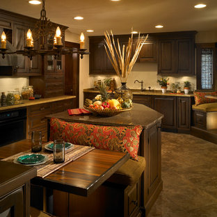 Photo of a large tropical l-shaped open plan kitchen in Other with an undermount sink, raised-panel cabinets, dark wood cabinets, granite benchtops, black appliances, ceramic floors and with island.