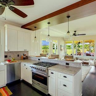 ハワイの中サイズのトロピカルスタイルのおしゃれなキッチン (エプロンフロントシンク、シェーカースタイル扉のキャビネット、白いキャビネット、御影石カウンター、茶色いキッチンパネル、石スラブのキッチンパネル、シルバーの調理設備、濃色無垢フローリング、アイランドなし、黒い床) の写真