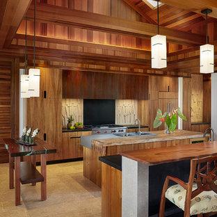 ハワイの広いトロピカルスタイルのおしゃれなキッチン (一体型シンク、フラットパネル扉のキャビネット、中間色木目調キャビネット、木材カウンター、マルチカラーのキッチンパネル、パネルと同色の調理設備、ライムストーンの床、ライムストーンのキッチンパネル) の写真