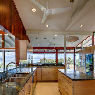 This is an example of a large midcentury u-shaped eat-in kitchen in Hawaii with a double-bowl sink, flat-panel cabinets, light wood cabinets, granite benchtops, stainless steel appliances, ceramic floors, with island and beige floor.