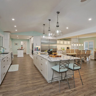 Photo of a large tropical open plan kitchen in Jacksonville with shaker cabinets, white cabinets, quartz benchtops, white splashback, ceramic splashback, stainless steel appliances, vinyl floors, multiple islands and grey benchtop.