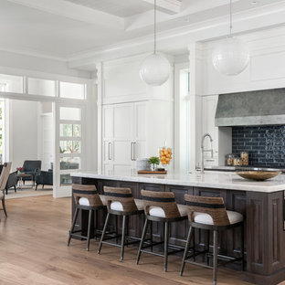 Inspiration for a tropical galley eat-in kitchen in Miami with raised-panel cabinets, dark wood cabinets, black splashback, white appliances, medium hardwood floors, with island, brown floor and white benchtop.
