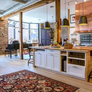 ボストンの小さいインダストリアルスタイルのおしゃれなキッチン (シェーカースタイル扉のキャビネット、白いキャビネット、大理石カウンター、ベージュキッチンパネル、石スラブのキッチンパネル、シルバーの調理設備、アンダーカウンターシンク、淡色無垢フローリング、茶色い床) の写真