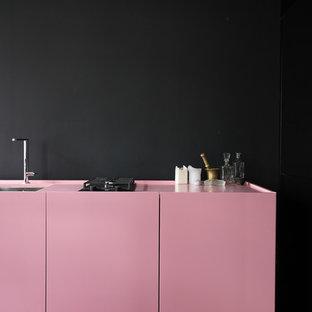 Ejemplo de cocina lineal, escandinava, de tamaño medio, cerrada, sin isla, con fregadero integrado, armarios con paneles lisos, puertas de armario rojas, suelo de cemento y suelo beige
