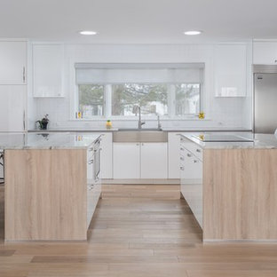 Expansive midcentury single-wall eat-in kitchen in Denver with a farmhouse sink, flat-panel cabinets, white cabinets, quartzite benchtops, white splashback, porcelain splashback, stainless steel appliances, light hardwood floors, multiple islands, brown floor and grey benchtop.