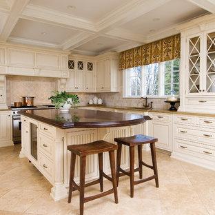 Diseño de cocina comedor en U, clásica, con encimera de madera, fregadero bajoencimera, puertas de armario blancas, salpicadero beige, electrodomésticos con paneles, suelo de travertino y salpicadero de piedra caliza