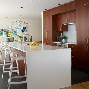 Exemple d'une cuisine moderne de taille moyenne avec un évier encastré, un placard à porte plane, des portes de placard en bois brun, un plan de travail en quartz modifié, une crédence en carreau de verre, un électroménager en acier inoxydable, un sol en ardoise, un îlot central, un sol gris et un plan de travail blanc.