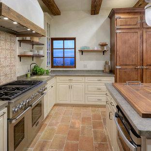他の地域の広い地中海スタイルのおしゃれなキッチン (ダブルシンク、レイズドパネル扉のキャビネット、ライムストーンカウンター、グレーのキッチンパネル、ライムストーンのキッチンパネル、シルバーの調理設備、テラコッタタイルの床、ピンクの床) の写真