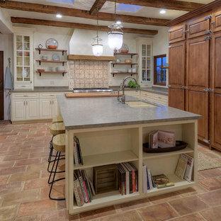Geschlossene, Große Mediterrane Küche in L-Form mit Doppelwaschbecken, profilierten Schrankfronten, Kalkstein-Arbeitsplatte, Küchenrückwand in Grau, Kalk-Rückwand, Küchengeräten aus Edelstahl, Terrakottaboden, Kücheninsel und rosa Boden in Sonstige