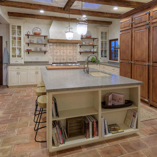 Design ideas for a large mediterranean l-shaped separate kitchen in Other with a double-bowl sink, raised-panel cabinets, limestone benchtops, grey splashback, limestone splashback, stainless steel appliances, terra-cotta floors, with island and pink floor.
