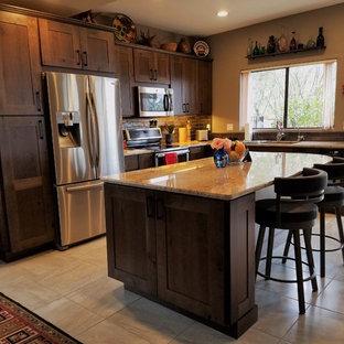 フェニックスの中サイズのサンタフェスタイルのおしゃれなキッチン (アンダーカウンターシンク、シェーカースタイル扉のキャビネット、グレーのキャビネット、御影石カウンター、茶色いキッチンパネル、ガラスタイルのキッチンパネル、シルバーの調理設備の、セラミックタイルの床) の写真