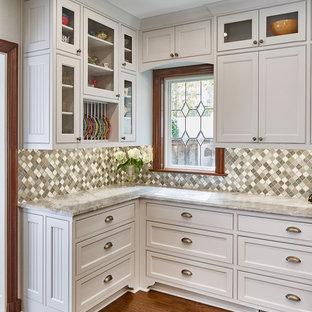 Cette image montre une cuisine traditionnelle en L fermée et de taille moyenne avec un évier encastré, un placard à porte shaker, des portes de placard blanches, une crédence grise, une crédence en mosaïque, un électroménager en acier inoxydable, un sol en bois brun, un îlot central, un sol marron et un plan de travail gris.