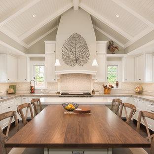 Стильный дизайн: п-образная кухня в классическом стиле с обеденным столом, врезной раковиной, фасадами с декоративным кантом, белыми фасадами, деревянной столешницей, разноцветным фартуком, фартуком из плитки мозаики, белой техникой, полом из бамбука и островом - последний тренд
