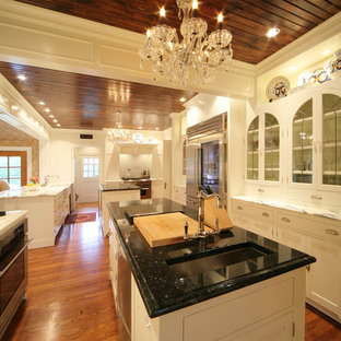 Large victorian u-shaped kitchen in Other with an undermount sink, recessed-panel cabinets, white cabinets, stainless steel appliances, medium hardwood floors and multiple islands.