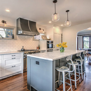Inspiration for a timeless dark wood floor kitchen remodel in Seattle with shaker cabinets, white cabinets, white backsplash, subway tile backsplash, stainless steel appliances and an island