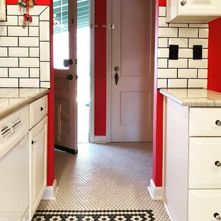 Photo of a mid-sized eclectic galley separate kitchen in Kansas City with raised-panel cabinets, white cabinets, marble benchtops, white splashback, subway tile splashback, white appliances, porcelain floors, no island, yellow floor and white benchtop.