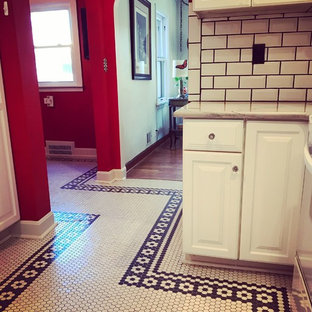 This is an example of a mid-sized eclectic galley separate kitchen in Kansas City with raised-panel cabinets, white cabinets, marble benchtops, white splashback, subway tile splashback, white appliances, porcelain floors, no island, yellow floor and white benchtop.