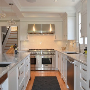 Enclosed kitchen - large transitional u-shaped medium tone wood floor enclosed kitchen idea in Ottawa with an undermount sink, shaker cabinets, white cabinets, granite countertops, white backsplash, subway tile backsplash, stainless steel appliances and an island