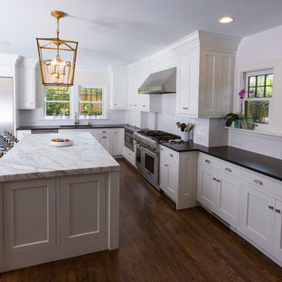 Mid-sized contemporary l-shaped open plan kitchen in Cincinnati with an undermount sink, shaker cabinets, white cabinets, soapstone benchtops, white splashback, subway tile splashback, stainless steel appliances, dark hardwood floors and with island.