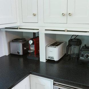 Offene, Mittelgroße Moderne Küche in L-Form mit Unterbauwaschbecken, Schrankfronten im Shaker-Stil, weißen Schränken, Speckstein-Arbeitsplatte, Küchenrückwand in Weiß, Rückwand aus Metrofliesen, Küchengeräten aus Edelstahl, dunklem Holzboden und Kücheninsel in Cincinnati