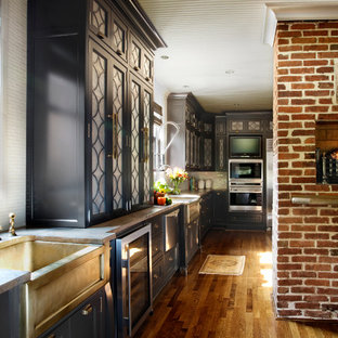 Design ideas for a traditional galley separate kitchen in Other with a farmhouse sink, stainless steel appliances, beaded inset cabinets, grey cabinets, limestone benchtops, white splashback, ceramic splashback, medium hardwood floors, with island and brown floor.