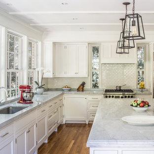 Пример оригинального дизайна: большая, узкая отдельная кухня в классическом стиле с врезной раковиной, фасадами в стиле шейкер, белыми фасадами, мраморной столешницей, белым фартуком, фартуком из плитки кабанчик, техникой из нержавеющей стали, островом, коричневым полом, паркетным полом среднего тона и серой столешницей