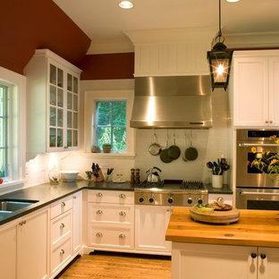 Geschlossene Klassische Küche in L-Form mit Triple-Waschtisch, Schrankfronten im Shaker-Stil, weißen Schränken, Speckstein-Arbeitsplatte, Küchenrückwand in Weiß, Rückwand aus Keramikfliesen, Küchengeräten aus Edelstahl, hellem Holzboden und Kücheninsel in Charlotte