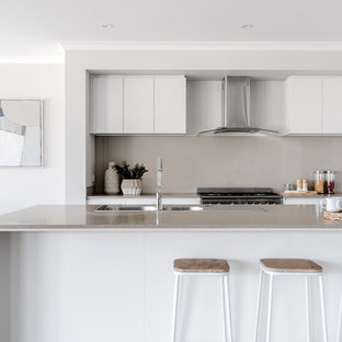 Photo of a contemporary galley open plan kitchen in Melbourne with flat-panel cabinets, white cabinets, an island and grey benchtop.