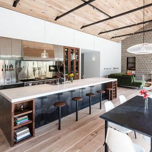 オースティンの大きいインダストリアルスタイルのおしゃれなキッチン (エプロンフロントシンク、フラットパネル扉のキャビネット、ステンレスキャビネット、メタリックのキッチンパネル、淡色無垢フローリング、ベージュの床、シルバーの調理設備の、メタルタイルのキッチンパネル、大理石カウンター) の写真