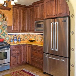 Cette image montre une cuisine méditerranéenne avec une crédence multicolore, un électroménager en acier inoxydable, un placard avec porte à panneau surélevé, des portes de placard en bois sombre, une crédence en carreau de céramique et un plan de travail jaune.