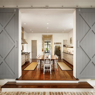 Large country galley medium tone wood floor eat-in kitchen photo in Houston with shaker cabinets, stainless steel appliances, beige cabinets and an island