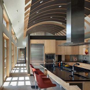シーダーラピッズの大きいコンテンポラリースタイルのおしゃれなキッチン (ドロップインシンク、フラットパネル扉のキャビネット、淡色木目調キャビネット、御影石カウンター、ガラスタイルのキッチンパネル、シルバーの調理設備の、ライムストーンの床、グレーのキッチンパネル、グレーの床) の写真