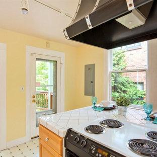 シアトルの中サイズのヴィクトリアン調のおしゃれなキッチン (アンダーカウンターシンク、シェーカースタイル扉のキャビネット、中間色木目調キャビネット、タイルカウンター、白いキッチンパネル、セラミックタイルのキッチンパネル、黒い調理設備、セラミックタイルの床) の写真