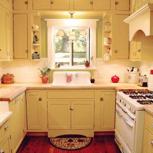 Diseño de cocina en U, campestre, pequeña, cerrada, sin isla, con armarios con rebordes decorativos, puertas de armario amarillas, encimera de madera, salpicadero blanco, electrodomésticos blancos, suelo de madera oscura y fregadero encastrado