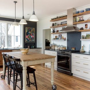 Mid-sized farmhouse kitchen inspiration - Mid-sized cottage l-shaped medium tone wood floor kitchen photo in Other with an undermount sink, shaker cabinets, white cabinets, soapstone countertops, black backsplash, stone slab backsplash, an island, black countertops and stainless steel appliances