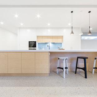 Idee per una grande cucina design con isola, lavello sottopiano, ante lisce, ante bianche, top in superficie solida, paraspruzzi blu, paraspruzzi con lastra di vetro, elettrodomestici in acciaio inossidabile e pavimento alla veneziana