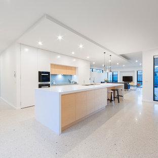 キャンベラの大きいコンテンポラリースタイルのおしゃれなキッチン (アンダーカウンターシンク、フラットパネル扉のキャビネット、白いキャビネット、人工大理石カウンター、青いキッチンパネル、ガラス板のキッチンパネル、シルバーの調理設備の、テラゾの床) の写真