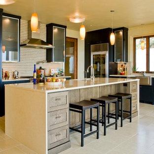 Cette image montre une cuisine américaine linéaire ethnique de taille moyenne avec un évier 2 bacs, un placard à porte shaker, des portes de placard noires, une crédence beige, un électroménager en acier inoxydable, un sol en travertin, un îlot central, un sol marron et un plan de travail beige.
