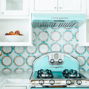 Offene, Kleine Maritime Küche in L-Form mit Unterbauwaschbecken, Kassettenfronten, weißen Schränken, Quarzwerkstein-Arbeitsplatte, bunter Rückwand, Rückwand aus Mosaikfliesen, bunten Elektrogeräten, braunem Holzboden und Kücheninsel in St. Louis