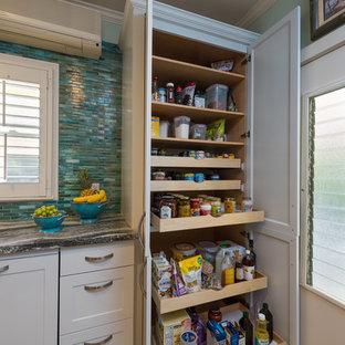 ハワイの中くらいのトロピカルスタイルのおしゃれな独立型キッチン (アンダーカウンターシンク、シェーカースタイル扉のキャビネット、白いキャビネット、珪岩カウンター、青いキッチンパネル、ガラスタイルのキッチンパネル、パネルと同色の調理設備、クッションフロア、アイランドなし、グレーの床) の写真