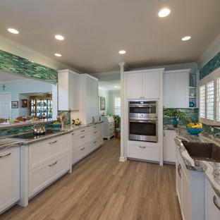 ハワイの中サイズのトロピカルスタイルのおしゃれな独立型キッチン (アンダーカウンターシンク、シェーカースタイル扉のキャビネット、白いキャビネット、珪岩カウンター、青いキッチンパネル、ガラスタイルのキッチンパネル、パネルと同色の調理設備、クッションフロア、アイランドなし、グレーの床) の写真