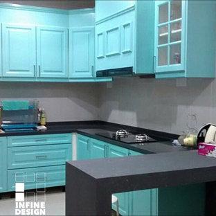 他の地域の中サイズのビーチスタイルのおしゃれなキッチン (ダブルシンク、インセット扉のキャビネット、中間色木目調キャビネット、人工大理石カウンター、ベージュキッチンパネル、磁器タイルのキッチンパネル、パネルと同色の調理設備、セラミックタイルの床) の写真