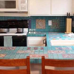 オレンジカウンティのエクレクティックスタイルのおしゃれなコの字型キッチン (フラットパネル扉のキャビネット、白いキャビネット、タイルカウンター、マルチカラーのキッチンパネル、セラミックタイルのキッチンパネル、黒い調理設備) の写真