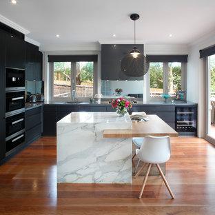 Réalisation d'une cuisine américaine design en L de taille moyenne avec un évier encastré, des portes de placard grises, un plan de travail en marbre, une crédence en carreau de miroir, un électroménager noir, un placard à porte plane, un sol en bois brun et 2 îlots.