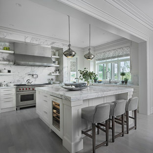 Transitional kitchen designs - Example of a transitional l-shaped gray floor kitchen design in Detroit with recessed-panel cabinets, white cabinets, gray backsplash, stainless steel appliances, an island and gray countertops