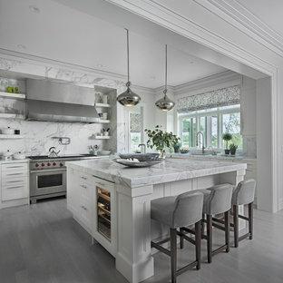 Inspiration pour une cuisine traditionnelle en L avec un placard avec porte à panneau encastré, des portes de placard blanches, une crédence grise, un électroménager en acier inoxydable, un îlot central, un sol gris et un plan de travail gris.