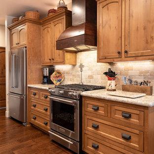 Medelhavsstil inredning av ett stort beige beige kök, med en nedsänkt diskho, luckor med infälld panel, skåp i mellenmörkt trä, bänkskiva i kvarts, beige stänkskydd, stänkskydd i stenkakel, rostfria vitvaror, mörkt trägolv, en köksö och brunt golv