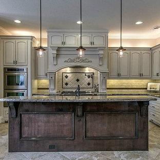 Foto på ett mellanstort medelhavsstil kök, med en nedsänkt diskho, vita skåp, granitbänkskiva, beige stänkskydd, stänkskydd i terrakottakakel, rostfria vitvaror, klinkergolv i porslin, en köksö och luckor med upphöjd panel