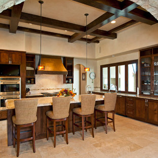 Large tuscan l-shaped ceramic floor and beige floor enclosed kitchen photo in Austin with glass-front cabinets, a drop-in sink, dark wood cabinets, granite countertops, beige backsplash, ceramic backsplash, stainless steel appliances and an island