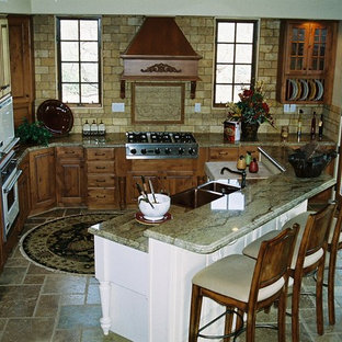 Mid-sized traditional eat-in kitchen appliance - Mid-sized elegant galley travertine floor eat-in kitchen photo in Phoenix with a farmhouse sink, raised-panel cabinets, medium tone wood cabinets, granite countertops, beige backsplash, stone tile backsplash, paneled appliances and an island